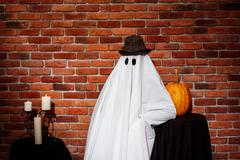 Ghost in hat posing over brick background. Halloween party Kuvituskuvat