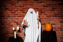 Ghost holding candle, stretching hand to camera. Halloween party Stock Photos