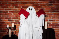 Ghost holding books over brick background. Halloween party Kuvituskuvat