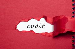 The word audit appearing behind torn paper Stock Photos