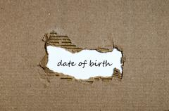 The word date of birth appearing behind torn paper Stock Photos