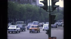 1969: cars moving on road trees around traffic signal people rushing buildings Stock Footage