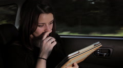Beautiful serious woman reading email on tablet in car Stock Footage