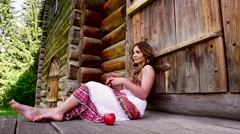 Beautiful fashion model sitting on the porch of a wooden house. Stock Footage