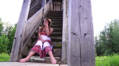 Beautiful fashion model sitting on the stairs in a wooden tower and posing fo Stock Footage