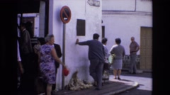 1969: footage of a busy street corner in a crowded town square. SPAIN Stock Footage
