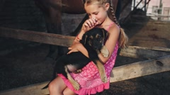 Curly Girl Caresses a Puppy in the Stables Stock Footage