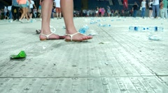 Lot of garbage, plastic bottles at the stadium, the girls legs are in the frame Stock Footage