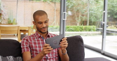 4k, Young African American man playing an online game on his touchscreen tablet  Stock Footage