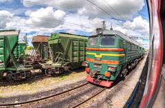 Freight train standing at a railway station in summer day Kuvituskuvat
