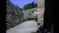 1969: people walking up to an ancient building on a tourist guide. SPAIN Stock Footage
