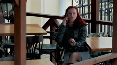 Girl Speaks on Cell Phone at Table in Empty Outdoor Cafe When Sun Stock Footage