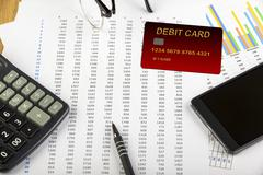 Debit card on a spread sheet with a calculator Stock Photos