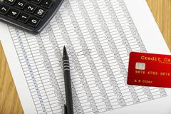 Red credit card laying on a spreadsheet with a calculator Stock Photos