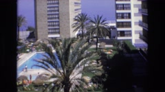 1969: people walk along the hotel pool deck on a sunny day. SPAIN Stock Footage