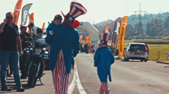 American family walk to their motorbike at a motorcycle parade Stock Footage