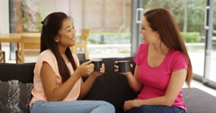 4k, Two young women sitting on the couch gossiping and drinking coffee. Stock Footage