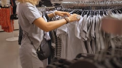 Shopping Woman Choosing Clothes in Clothing Store Arkistovideo