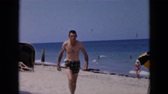 1956: beach-goers walk on sandy beach and a woman removes her swimming cap CUBA Stock Footage