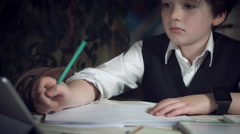 4K Hi-Tech Shot of a Child Doing Homework and Checking his Tablet Stock Footage