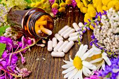 Capsules in open brown jar on board with flowers Stock Photos