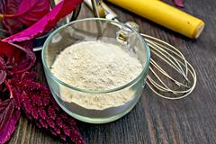 Flour amaranth in cup with rolling pin on board Stock Photos