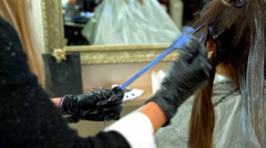 The hairdresser applies the paint to the hair Stock Footage