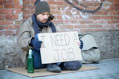 Homeless seated in the street and asking for a job Stock Photos