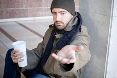 Homeless seated in the street and asking for charity Stock Photos