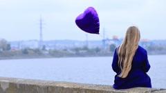 Sad girl with broken heart holding heart balloon Stock Footage