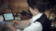 4K Hi-Tech Shot of a Child Doing Homework with Help from Tablet Stock Footage