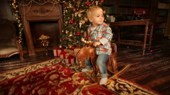 Boy with toy horse near Christmas and New Year tree 2017 Stock Footage