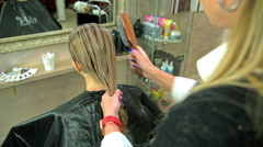 Hairdresser combs her hair Stock Footage