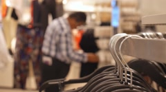 Man Shopping for Clothes at Clothing Store. Clothes on Hangers Closeup Stock Footage