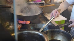 Asian Cook Cooking Street Food with Wok and Frying Pan on Gas Flame Stock Footage