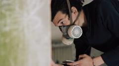4K Masked graffiti artist using image on smartphone to copy artwork onto wall Stock Footage