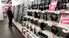 Young woman chooses earphones in electronics store Stock Footage