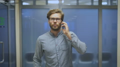 Young man walks down the hallway and talking on the phone Stock Footage