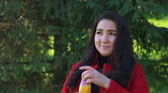 Girl in a red coat drinking orange juice Stock Footage