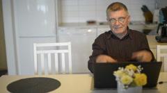 Happy senior man using laptop computer Stock Footage
