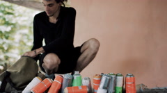 4K Graffiti artist sets out spray cans in front of wall with painted background Stock Footage