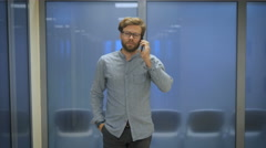 Office Manager is a long corridor and talking on the phone Stock Footage