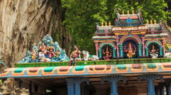 Camera Moves from Pavilion Roof to Muragan Statue in Batu Caves Stock Footage