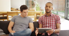 4K Male friends relaxing at home looking at tablet & having serious conversation Stock Footage