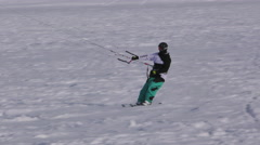 A snowkiter surfing and jumping on a frozen lake in the Switzerland Alps Stock Footage