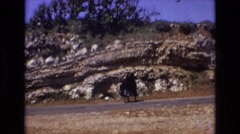 1972: two ladies black robe walking down road hilly area green trees around  Stock Footage