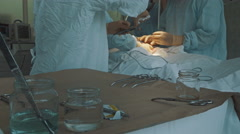 A surgical tool is handed to a surgeon in an operating room Stock Footage
