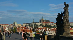 Tourist visiting Charles Bridge on a sunny day. Prague Castle and Saint Vitus Stock Footage