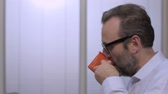 Businessman with glasses drinking coffee in the office Stock Footage