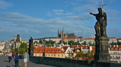 Tourists visiting Charles Bridge on a sunny day. Prague Castle and Saint Vitus Stock Footage